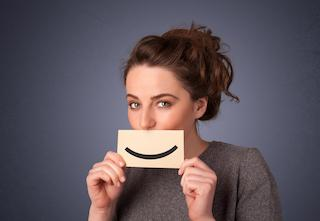 a woman holds a smile sign in front of her mouth | zoom teeth whitening orlando